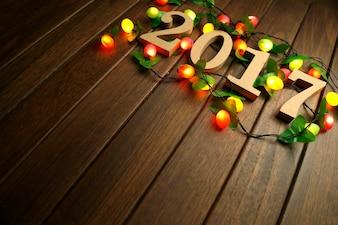 2017 Happy New Year, hölzerne Figuren und blinkende Lichter auf dem Retro-Desktop
