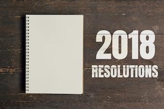 2018 Auflösungen und Brown Notizbuch offen auf Holz Tisch Hintergrund mit Platz.
