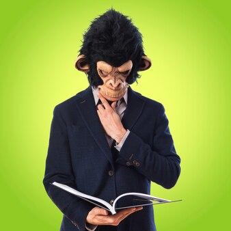 Affe Mann liest Buch auf buntem Hintergrund