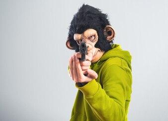 Affe Mann schießt mit einer Pistole