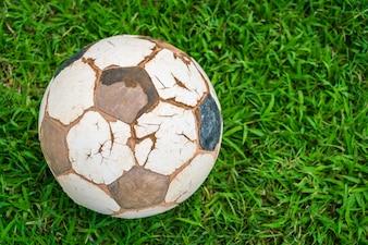 Alte Fußballkugel auf frischem grünen Gras Frühjahr