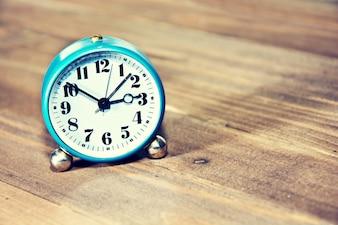 Alte Uhr auf dem hölzernen Hintergrund.