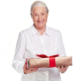 Ältere Frau, die ein Geschenk mit einer roten Schleife hält