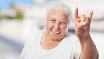 Ältere Frau, die Hörner mit den Händen
