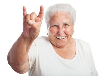 Ältere Frau, die Hörner mit der Hand lächelnd