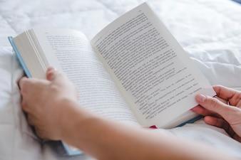 Arme mit Buch auf dem Bett