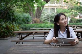 Asiatische Frau mit Tablette und Musik hören