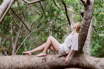 Attraktive junge Frau auf einem Stamm aufwirft