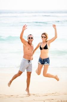 Aufgeregtes junges Paar springt am Strand