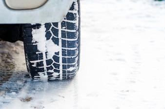 Autoreifen auf Winterstraße mit Schnee bedeckt. Fahrzeug auf schneebedeckten Gasse am Morgen bei Schneefall