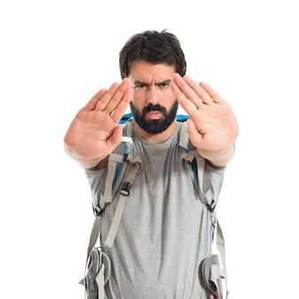 Backpacker machen Stop-Schild über weißem Hintergrund