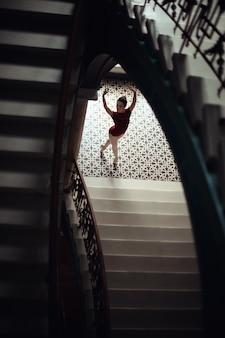 Ballerina in einem roten Kleid von einer Treppe gesehen