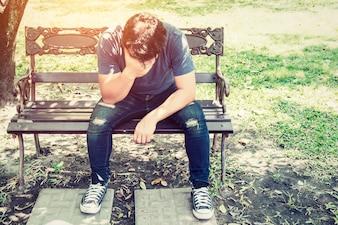 Besorgter Mann sitzt auf einer Bank