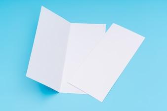 Bifold weiße Vorlage Papier auf blauem Hintergrund.