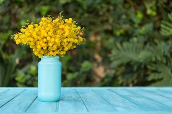 Blaue hölzerne Oberfläche mit Blumen auf einer Vase