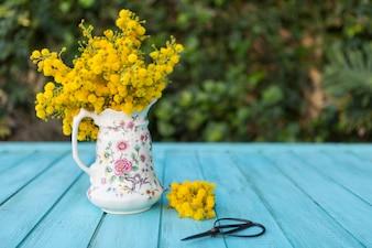 Blaue hölzerne Oberfläche mit Vase, Blumen und Schere