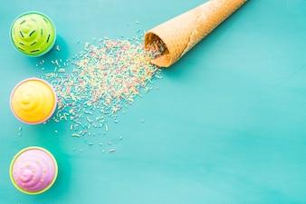 Blauer Hintergrund mit Eis Kegel und Cupcakes