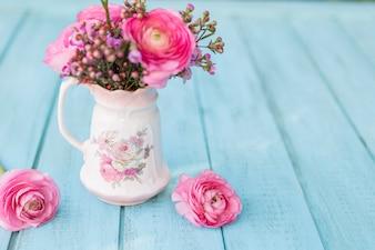 Blauer Hintergrund mit rosa Blüten und dekorative Vase