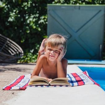 Blonde Junge liegt auf Bauch von Pool