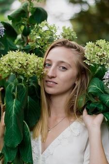Blonde Mädchen posiert mit Blumen neben ihr Gesicht