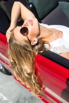Blonde schöne Frau in Sonnenbrille sitzt im roten Auto am Meer. Seeblick. Urlaubskonzept. Glücklich Freiheit. Road Trip an schönen sonnigen Sommertag