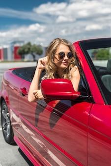 Blonde schöne Frau in Sonnenbrille sitzt im roten Auto am Meer. Urlaubskonzept. Glücklich Freiheit. Road Trip an schönen sonnigen Sommertag
