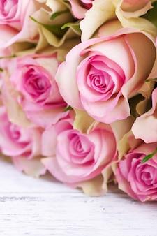 Blumenstrauß aus rosa Rosen mit blauem Band auf einem Vintage-Holz-Hintergrund