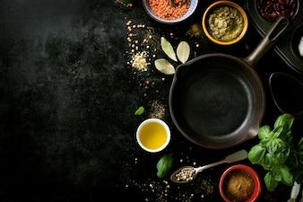 Bratpfanne leer mit verschiedenen Gewürzen in einem schwarzen Tisch