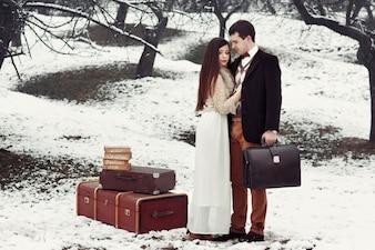 Braut und Bräutigam mit altmodischem Koffer stehen im Winterpark