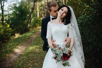Bräutigam umarmt Braut hält Bouquet