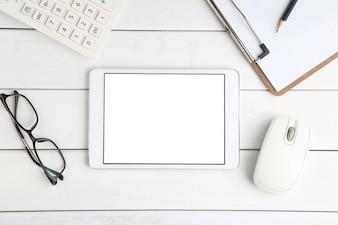 Brille, Taschenrechner und Tablette auf weissem Schreibtisch