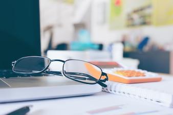 Brillen auf Laptop-Tastatur und Tagebuch auf Holztisch
