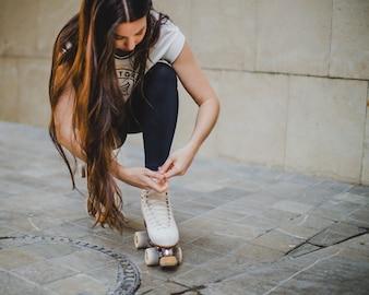 Brunette Mädchen hockend Binden Rollerskates draußen