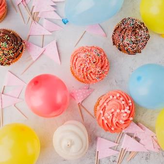 Bündel von Fahnen und Ballons in der Nähe von Cupcakes