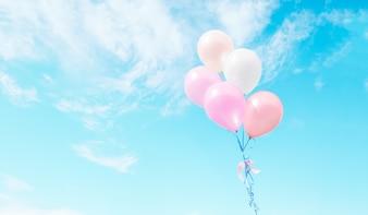 Bunte Luftballons fliegen am Himmel.