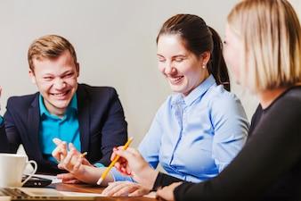 Büroangestellte sitzen am Schreibtisch lächelnd