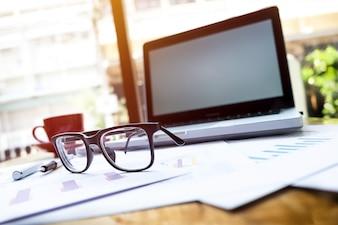 Büroarbeitsplatz mit Laptop und Gläser auf Holztisch