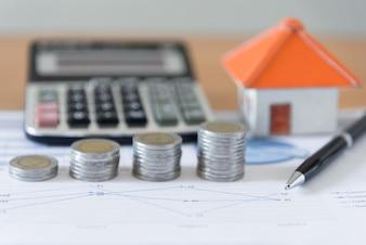Business-Dokument Diagramm Schreibtisch Hintergründe mit Münzen Stapel, Papierhaus, Taschenrechner und Stift