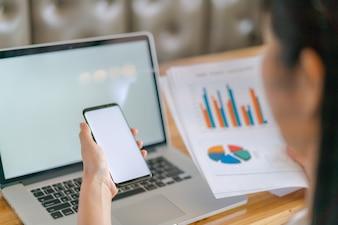 Business-Frau Hand mit finanziellen Charts und Handy über Laptop auf dem Tisch.
