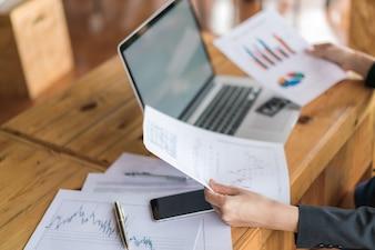 Business-Frau Hand mit finanziellen Charts und Laptop auf dem Tisch.