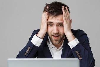 Business-Konzept - Porträt gut aussehend stressigen Geschäftsmann in Anzug Schock Blick auf Arbeit im Laptop. Weißer Hintergrund.