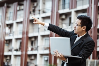 Business-Konzept - Young Business Mann planen Projekt auf seinem Eigentum mit Laptop.