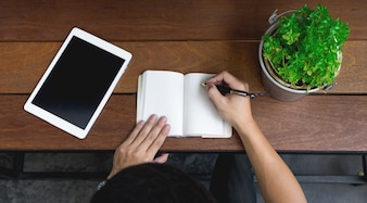 Business-Mann Hand mit Laptop und schreiben Notiz inspirieren Idee auf Holz Schreibtisch, Startup-Konzept. Draufsicht