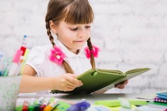 Charmantes Mädchen genießt das Lesen von Lehrbuch