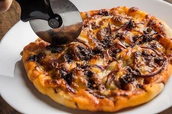 Chef schneidet frisch zubereitete Pizzaschnecken