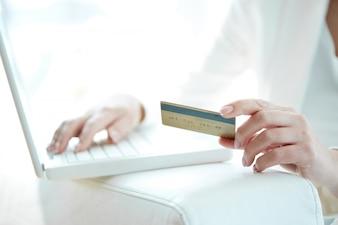 Close-up der Frau, die online mit Kreditkarte einkaufen und Laptop