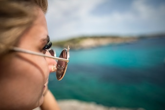 Close up der schönen Frau beobachten am Meer durch ihre Sonnenbrille