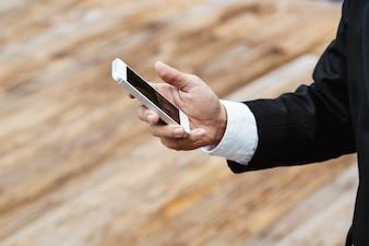 Close-up smart Business-Mann mit modernen schwarzen Anzug und weißen Hemd und SMS auf mobilen Smartphone