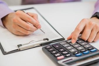 Close-up von Geschäftsmann Berechnung Rechnungen mit Taschenrechner