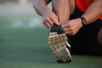 Close-up von männlichen Händen binden Sportschuhe